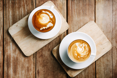 capuchino: enfoque selectivo taza de café caliente arte del latte en la mesa de madera, se centran en la espuma blanca Foto de archivo