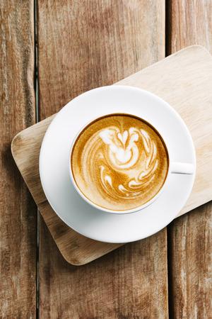Selectieve aandacht kopje hete latte art koffie op houten tafel