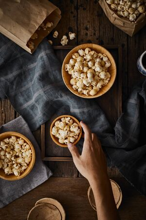 Delicious popcorn with caramel on wooden background.