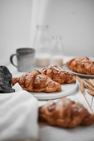 Almond croissant with custard filling on wood background.