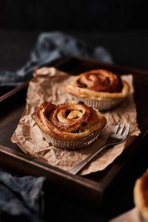 Fresh danish pastry with raisins on wood background.Tasty sweet bakery.