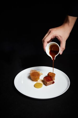 Hand pouring sauce over food on a plate, exquisite dish, creative restaurant meal concept