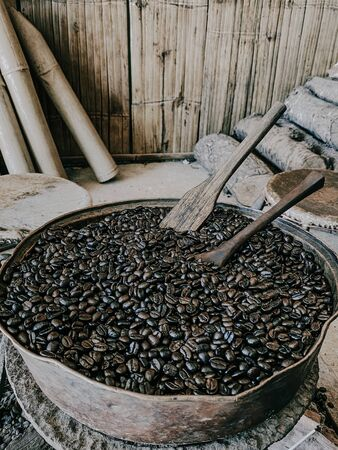 Traditional coffee roasting in metal basin with wooden spoon at hill tribe village in the northern of Thailand.