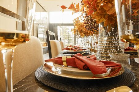 Table setting with autumn decorations, glasses and plates. Holidays, catering and hospitality concept.