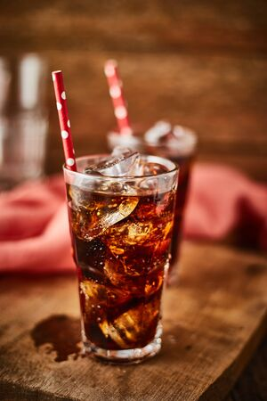 Close up glass of refreshing cola with ice on table.