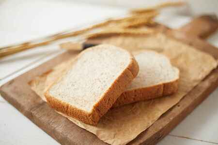 Whole wheat bread baked on wooden background.