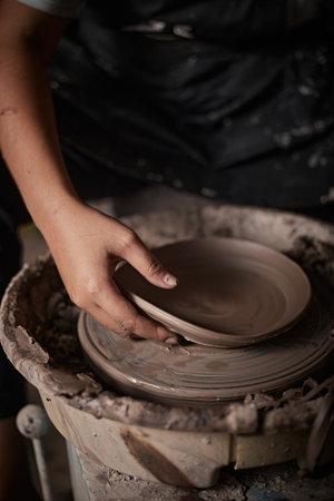 Hands of craftsman artist working on pottery wheel.Selective Focus