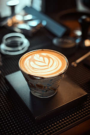 A cup of latte art coffee in the shape of wing tulip with foam on wooden table