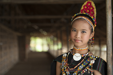 Kudat, Sabah Malaysia. April 10, 2013: A young lady from Rungus ethnic wearing traditional costume poses for the camera during the local Festival celeberation in Kudat, Sabah. Rungus tribe popular with colorful costume with a lot of beads.