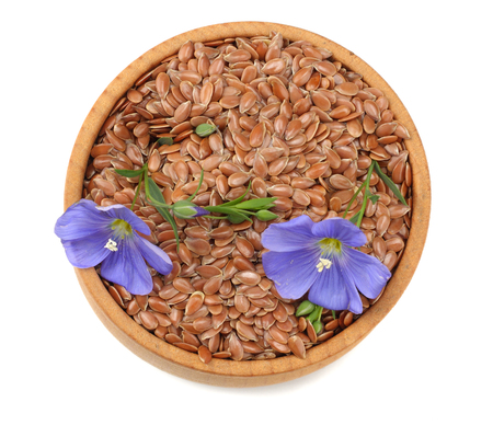 flax seeds in wooden bowl with flower isolated on white background. flaxseed or linseed. Cereals. top view Zdjęcie Seryjne