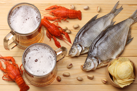 Glass beer with crawfish and dried fish on light wooden background. Beer brewery concept. Beer background. top view