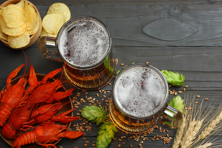 Glass beer with crawfish, hop cones and wheat ears on dark wooden background. Beer brewery concept. Beer background. top view with copy space