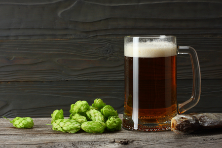 Glass beer with hop cones and dried fish on dark wooden background. Beer brewery concept. Beer background Stockfoto