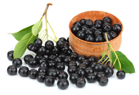 Chokeberry with leaf in wooden bowl isolated on white background. Black aronia