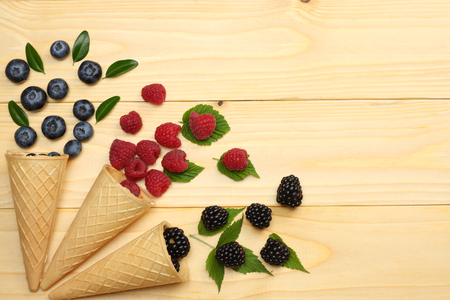 mix of blueberries, blackberries, raspberries in ice cream cone on light wooden table background. top view with copy space