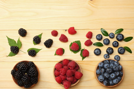 mix of blueberries, blackberries, raspberries in wooden bowl on light wooden table background. top view with copy space