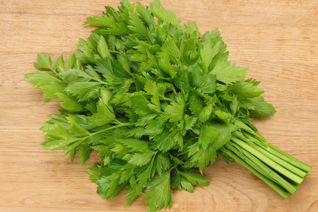 celery leaves on wooden table. Healthy food. 免版税图像