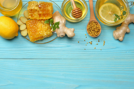 healthy background. honey, honeycomb, lemon, tea, ginger on blue wooden table. Top view with copy space