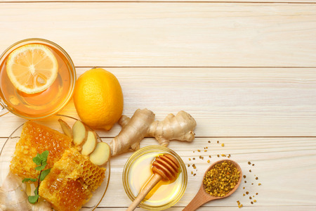 healthy background. honey, honeycomb, lemon, tea, ginger on white wooden table. Top view with copy space Foto de archivo