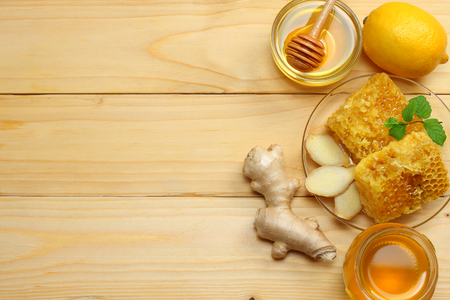 healthy background. honey, honeycomb, lemon, tea, ginger on light wooden table. Top view with copy space