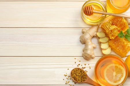healthy background. honey, honeycomb, lemon, tea, ginger on white wooden table. Top view with copy space 版權商用圖片
