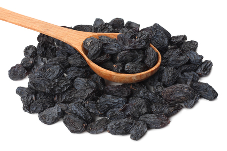 uvetta nera in cucchiaio di legno isolato su sfondo bianco