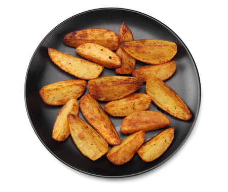 Fried potato wedges on black plate isolated on white background. top view. Fast food