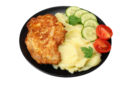Mashed potatoes with schnitzel on black plate isolated on white background