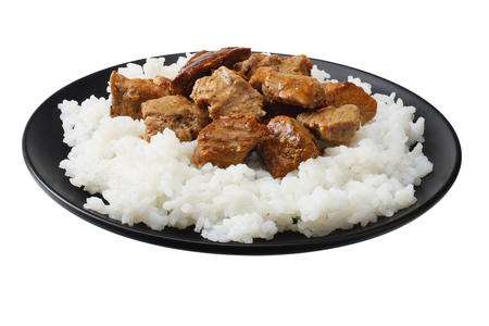 black plate with white rice and goulash isolated on white background Stock Photo
