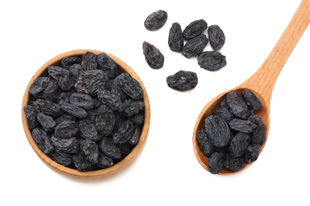 black raisins in wooden bowl isolated on white background. top view
