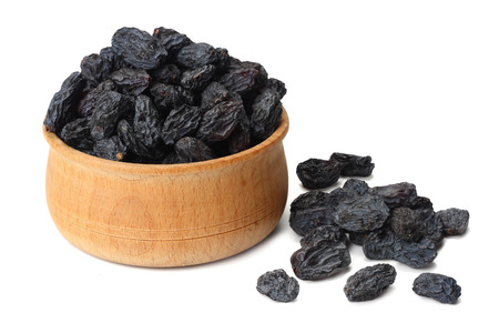 black raisins in wooden bowl isolated on white background