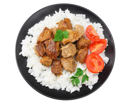 black plate with white rice and goulash isolated on white background. top view