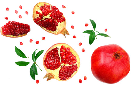 piece of pomegranate with seeds and green leaves isolated on a white background. top view