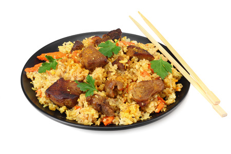 pilaf with meat on black plate isolated on white background