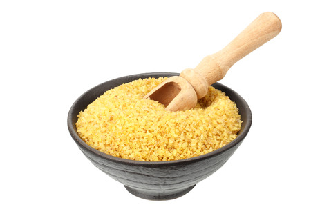 dry bulgur wheat in bowl isolated on white background