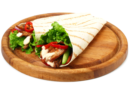 Tortilla wrap with fried chicken meat and vegetables on wooden board isolated on white background