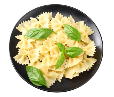black plate of pasta farfalle isolated on white background. top view.