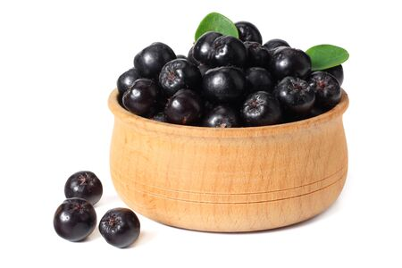 Chokeberry in wooden bowl with green leaves isolated on white background. Black aronia