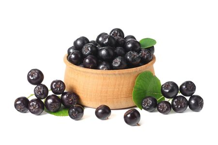 Chokeberry in wooden bowl with green leaves isolated on white background. Black aronia Zdjęcie Seryjne