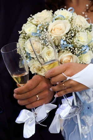 bride and groom holding hands at wedding glasses photo