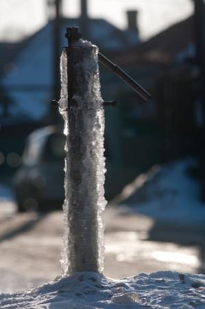 watertap: frozen water-tap on ice rock Stock Photo