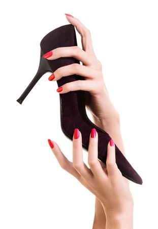 tacones rojos: Hermosas manos con uñas de color rojo la celebración de tacón alto