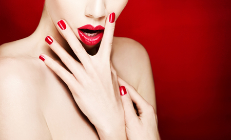 Makeup and cosmetic image. Red lips and manicure. Isolated on red background with copy space. Imagens