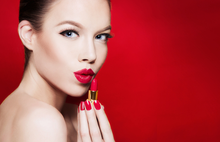 Beautiful woman portrait... Red lips holding a lipstick. isolated on red background. Fashion beauty portrait with copy space.