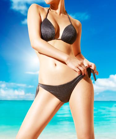 traje de baño: Mujer con bikini negro en la playa. hermosa piel bronceada.