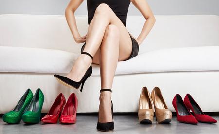 tienda de zapatos: Hermosa la pierna de la mujer sentada en el sofá con muchos zapatos de tacón alto. Foto de archivo