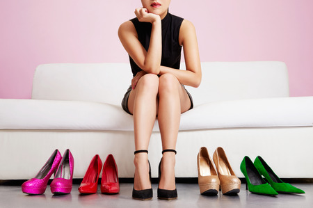 green couch: Woman choosing shoes or trouble with high heels.