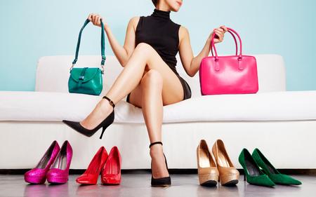 moda: Sapatas coloridas e sacos com mulher sentada no sofá.