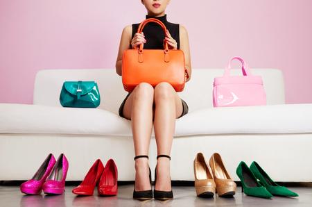 shoe store: zapatos de colores y bolsas con mujer sentada en el sofá.