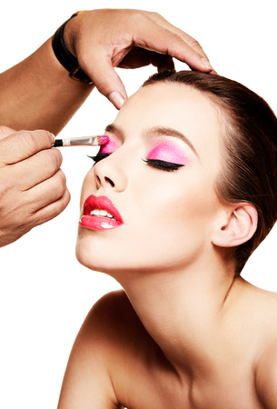 Makeup artist putting pink eye shadow on the beautiful woman. Imagens